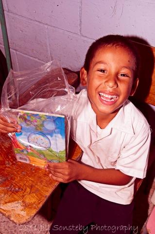 A little boy smiling at the school supplies we gave him - Utila, Honduras