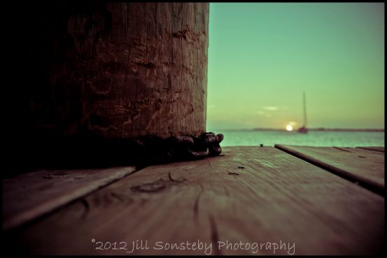 A sunset in the background of a chain on a dock in Utila, Honduras