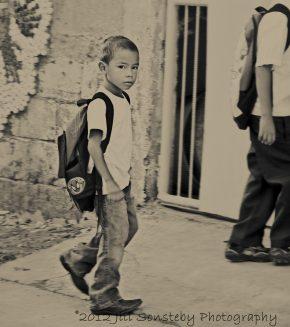 A little boy without a uniform walks into the school gate in Utila, Honduras.