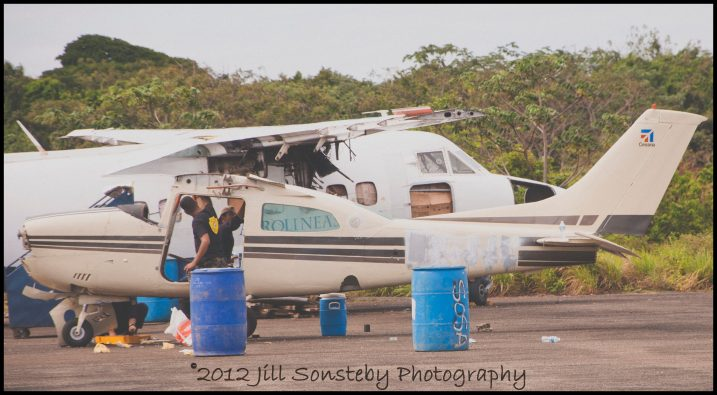 Police officials strip an abandoned airplane on the airport tarmac of Utila, Honduras