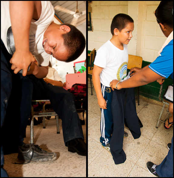 A boy is helping his little brother try on shoes and the next day he received a new uniform too!