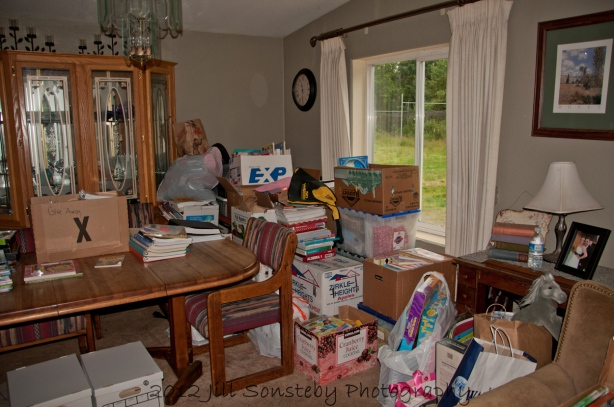 Collection of books in my sister's dining room, waiting to be shipped to Utila, Honduras.