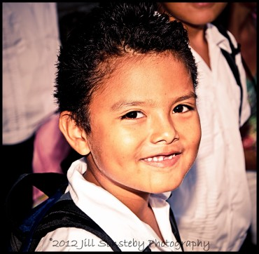 A smiling young boy poses to have his picture taken at the public school (CEBRH) in Utila, Honduras.