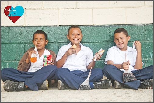 3 boys sitting down on the walkway eating lunch at school in Utila, Honduras at the public school